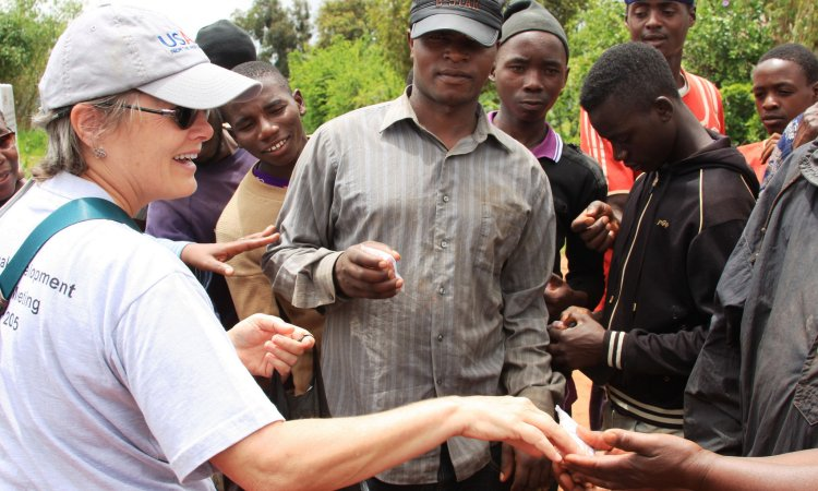Joan Mayer of USAID hands out packets of improved seeds